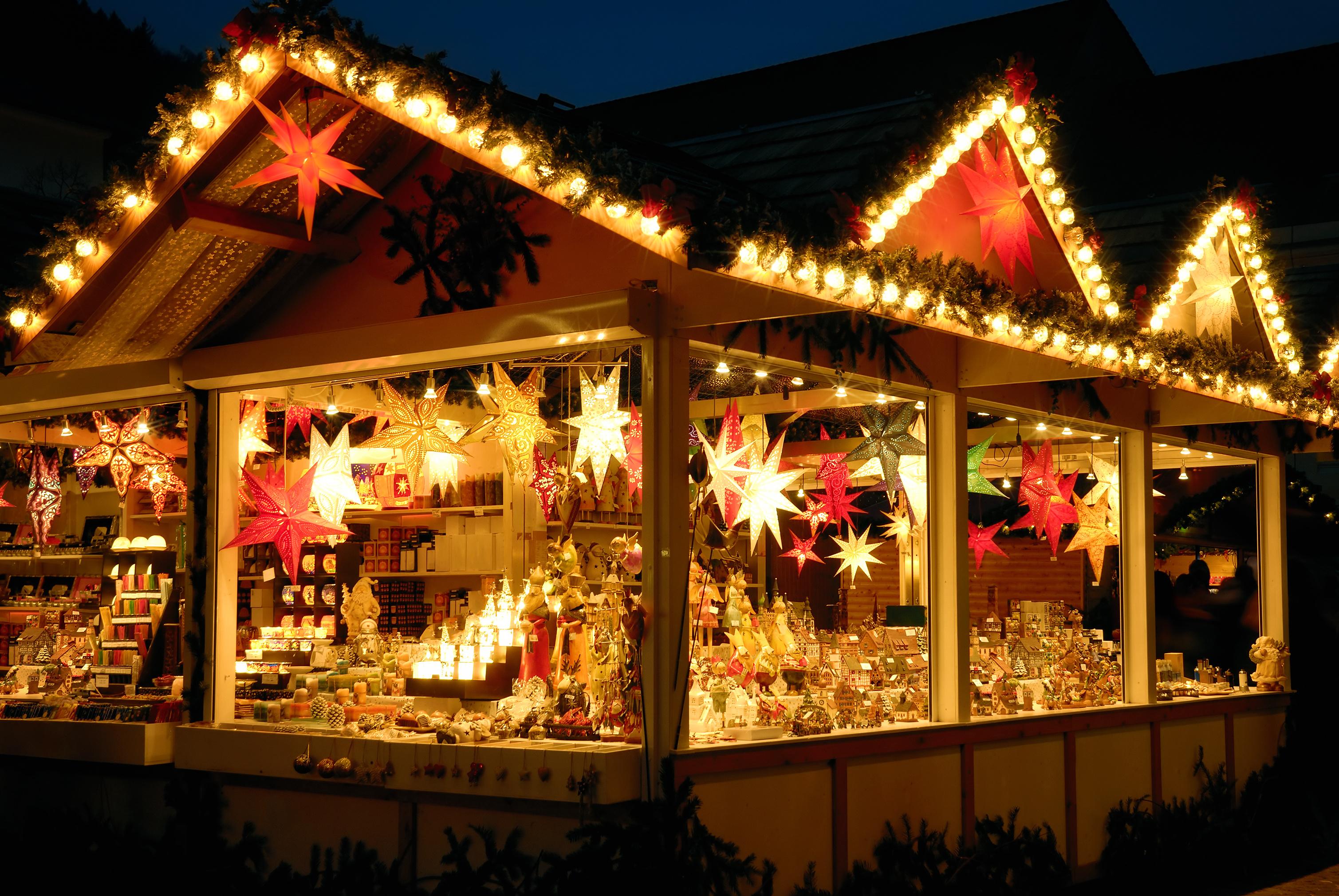 Bunt leuchtender Verkaufsstand am Weihnachtsmarkt mit vielen Dekowaren, keine Logos